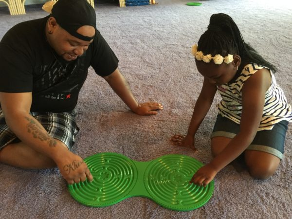 father and daughter with green plastic Chartres Intuipath double finger labyrinth